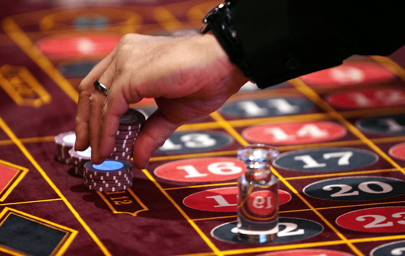 Roulette dealer picking chips after placement of win marker